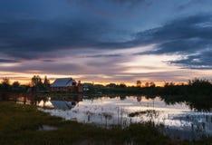 Härligt landskap med brännhet solnedgång över sjön i by Royaltyfri Foto