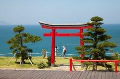 Härligt landskap med den röda japanska religiösa porten i en parkera på en kust royaltyfria foton