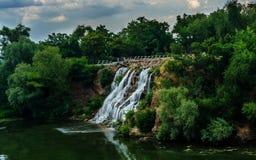 Härligt landskap med en naturlig vattenfall Strömmar av bubblandevatten Ett naturligt landskap med träd, vatten, en vattenfall Royaltyfri Bild