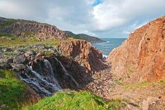 Härligt landskap med en vattenfall, vaggar och havet Arkivbilder