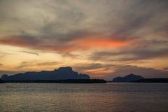 Härligt landskap med höga berg med upplysta maxima, stenar i bergsjön, reflexion, blå himmel och gult solljus royaltyfri fotografi