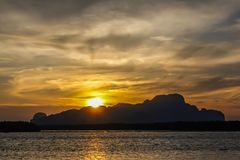 Härligt landskap med höga berg med upplysta maxima, stenar i bergsjön, reflexion, blå himmel och gult solljus royaltyfria foton