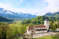 Härligt landskap med kyrkan i Gruyeres, Schweiz Fjällängberg och fält, nätt sommardag arkivfoton
