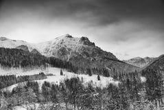 Härligt landskap Snöig berg och stormmoln Arkivfoto