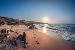 Härligt landskap, stenig havsfjärd på solnedgången med fotspår i sanden arkivbild