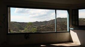 Härligt landskap ut ur brett fönster av ett övergett hotell arkivfilmer