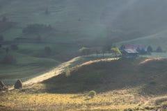 Härligt lantligt berglandskap i morgonljuset med dimma, gamla hus och höstackar Fotografering för Bildbyråer