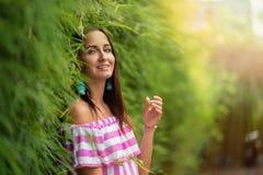 Härligt le för ung kvinna som står på det gröna staketet, i solen royaltyfria bilder