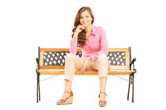 Härligt le kvinnasammanträde på en bänk och se kameran Arkivbild