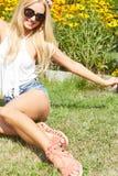 Härligt le kvinnasammanträde på ett utomhus- gräs Royaltyfri Foto