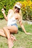 Härligt le kvinnasammanträde på ett utomhus- gräs Royaltyfria Foton