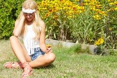 Härligt le kvinnasammanträde på ett utomhus- gräs Arkivfoto