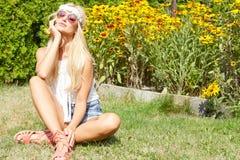 Härligt le kvinnasammanträde på ett utomhus- gräs Arkivbild