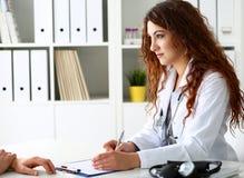 Härligt le kvinnligt doktorssamtal med patienten fotografering för bildbyråer