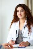 Härligt le kvinnligt doktorssamtal med patienten arkivbilder