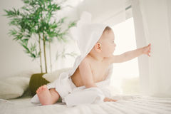 Härligt le som är nyfött, behandla som ett barn pojken som täckas med den vita bambuhandduken med roliga öron Sitta på en vit rät Arkivbilder
