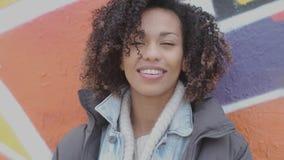 H?rligt le ungt womant med afro posera f?r frisyr som ?r utomhus- med grafitti stock video