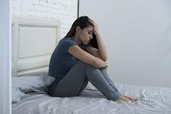 Härligt ledset och deprimerat latinskt kvinnasammanträde på säng frustrerade hemma lidandefördjupning arkivfoton