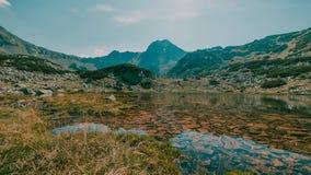 härligt liggandeberg En sjö som omges av berg i den Retezat nationalparken fotografering för bildbyråer