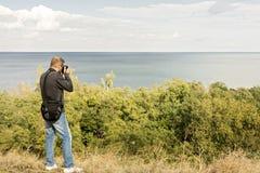härligt liggandehav En man fotograferar havet och himlen Royaltyfri Bild