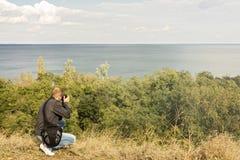 härligt liggandehav En man fotograferar havet och himlen Royaltyfri Fotografi
