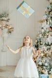 Härligt liten flickaanseende nära julgranen och thro fotografering för bildbyråer