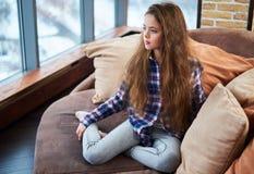 Härligt liten flickasammanträde på en soffa royaltyfri foto