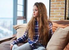 Härligt liten flickasammanträde på en soffa arkivfoton