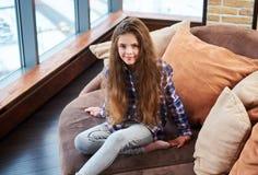 Härligt liten flickasammanträde på en soffa arkivbilder