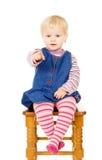 Härligt liten flickasammanträde på en stol arkivfoton