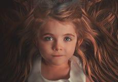 Härligt litet barn med långt hår fotografering för bildbyråer