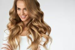 härligt lockigt hår Flicka med den krabba långa hårståenden volym royaltyfria foton