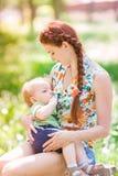 Härligt lyckligt amma för moder som är utomhus- Arkivbild