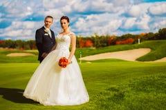 Härligt lyckligt gift par på golffält fotografering för bildbyråer