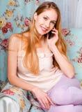 Härligt lyckligt ungt blont flickasammanträde på den talande nollan för soffa royaltyfri bild