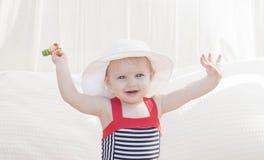 Härligt lyckligt uttrycksfullt blont flickalitet barn i en Cabana med solskydd royaltyfria bilder
