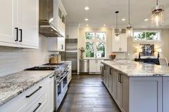 Härligt modernt kök i lyxig hemmiljö med ön och arkivbild