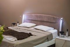 Härligt modernt märkes- sovrum i pastellfärgade mörka färger Bekväm säng i hotellet royaltyfri foto