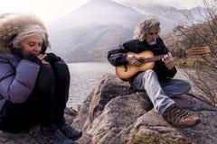 Härligt mogna par som spelar ett gitarrsammanträde på sjön fotografering för bildbyråer