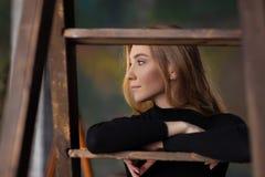 Härligt nätt anseende för ung kvinna som lutar på stegen I Royaltyfri Fotografi
