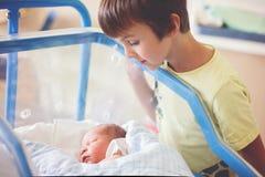 Härligt nyfött behandla som ett barn pojken som lägger i lathund i före födseln sjukhus, royaltyfria foton