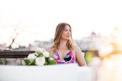 Härligt och charmigt sitta för kvinna som är utomhus- royaltyfri bild