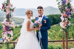 Härligt och le ungdomar poserar under en blommabåge under en storartad natur En flicka i en bröllopsklänning Arkivbild