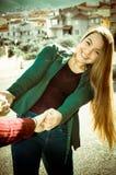 Härligt och när du ler unga flickan rymmer händer av dra för vän hennes och att dansa Arkivfoton