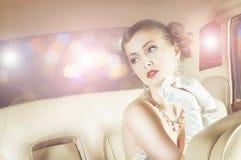 Härligt och rikt världsstjärnaflickasammanträde i en retro bil arkivbild