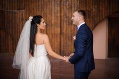 Härligt och ungt gift par som rymmer händer för en anothers royaltyfri bild
