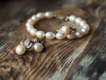 Härligt pärlemorfärg armband och örhängen på elegant bakgrund, slut upp grunt djupfält Royaltyfria Bilder