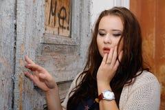 Härligt plus formatkvinna uttrycker fröjd mot en dörr royaltyfria foton