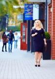 Härligt plus formatkvinnan som går stadsgatan arkivbilder