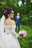 Härligt plus formatmodellkvinna med att gifta sig frisyren i en trendig bröllopsklänning som poserar för den gifta sig ceremonin royaltyfri fotografi
